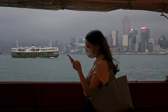 In this Thursday, May 28, 2020, photo, a woman uses a smartphone on a ferry in Hong Kong. Hong Kong has been living on borrowed time ever since the British made it a colony nearly 180 years ago, and all the more so after Beijing took control in 1997, granting it autonomous status. A national security law approved by China's legislature Thursday is a reminder that the city's special status is in the hands of Communist Party leaders who have spent decades building their own trade and financial centers to take Hong Kong's place. (AP Photo/Kin Cheung)