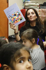 In this Jan. 23, 2019, photo, Bahareh Hedyahe leads Persian story time at Irvine public library in Irvine, Calif. It's been four decades since the Iranian revolution overthrew the ruling shah, prompting tens of thousands of Iranian exiles and refugees to make their lives in the United States. Years later, they have set down roots here and are finding ways to pass their love of Iranian culture to their American children and grandchildren. (AP Photo/Chris Carlson)