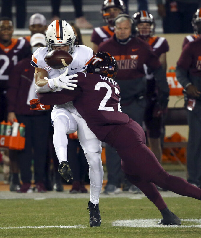Virginia Tech's Chamarri Connerm right, hits Virginia's Billy Kemp IV, knocking the ball loose during the first half of an NCAA college football game Saturday, Dec. 12, 2020, in Blacksburg, Va. (Matt Gentry/The Roanoke Times via AP, Pool)