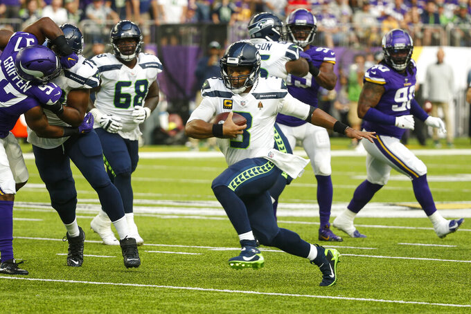Seattle Seahawks quarterback Russell Wilson (3) runs against the Minnesota Vikings in the first half of an NFL football game in Minneapolis, Sunday, Sept. 26, 2021. (AP Photo/Bruce Kluckhohn)