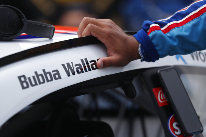 Driver Bubba Wallace leans on his car in the pits of the Talladega Superspeedway prior to the start of the NASCAR Cup Series auto race at the Talladega Superspeedway in Talladega Ala., Monday June 22, 2020.  (AP Photo/John Bazemore)