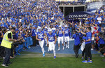 FILE - BYU football players enter the field to warm up for an NCAA college football game against Utah in Provo, Utah, in this Thursday, Aug. 29, 2019, file photo. A deal BYU has made available to its football players could test how much allowing athletes to be compensated by outside companies for name, image and likeness can be used as a competitive advantage. On Thursday, Aug. 12, 2021, BYU announced Built Brands —- a Utah-based company that makes protein-heavy snacks —- will give the opportunity for all 123 members of its football team to be paid to promote its products. (AP Photo/George Frey, File)