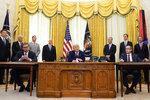 President Donald Trump speaks after participating in a signing ceremony with Serbian President Aleksandar Vucic, seated left, and Kosovar Prime Minister Avdullah Hoti, seated right, in the Oval Office of the White House, Friday, Sept. 4, 2020, in Washington. (AP Photo/Evan Vucci)