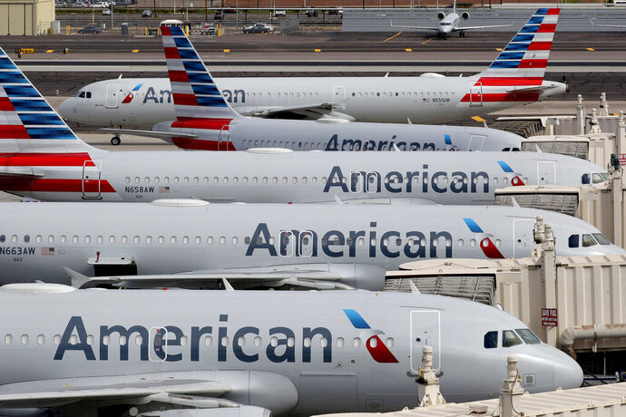 FILE - In this March 25, 2020, file photo, American Airlines jets sit idly at their gates as a jet arrives at Sky Harbor International Airport in Phoenix. American Airlines is telling 25,000 workers that they could lose their jobs in October because of the sharp drop in air travel during the virus pandemic. The airline said Wednesday, July 15, it was starting new offers of buyouts and partially paid leave, which it hopes will reduce the number of furloughs. (AP Photo/Matt York, File)