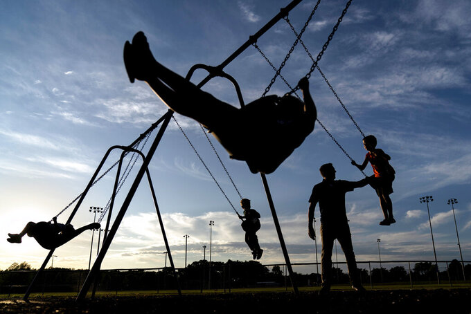 "State Republican Sen. Roger Roth, pushes his four sons on a park's swing set in Appleton, Wis., Aug. 19, 2020. Republicans here say there is proof that their playbook of aiding companies with tax breaks can protect jobs and provide a foundation for growth. They point to the saving of the nearby Kimberly-Clark plant in Cold Springs through tax incentives and union concessions. ""It's bigger than just 400 jobs, it's the footprint of 198 other businesses, a whole ecosystem,"" Roth said. (AP Photo/David Goldman)"