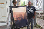 FILE - In this Sept. 3, 2020, file photo, Joe Prude, brother of Daniel Prude, right, and his son Armin, stand with a picture of Daniel Prude in Rochester, N.Y. Daniel Prude, 41, suffocated after police in Rochester put a