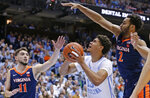 North Carolina's Cameron Johnson (13) looks to shoot while Virginia's Ty Jerome (11) and Braxton Key (2) defend during the first half of an NCAA college basketball game in Chapel Hill, N.C., Monday, Feb. 11, 2019. (AP Photo/Gerry Broome)