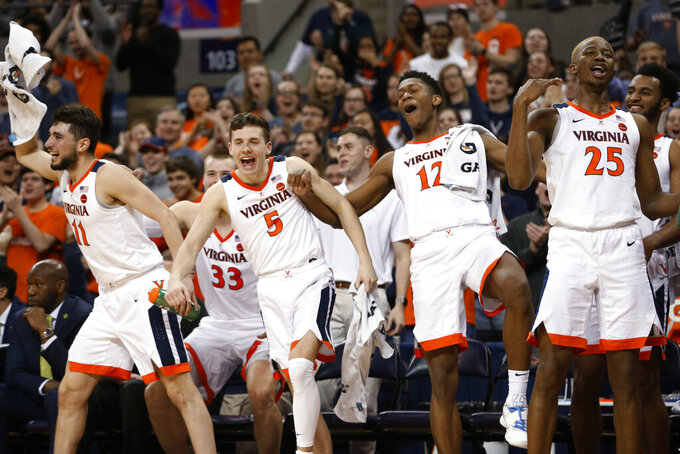 Virginia guard Ty Jerome, left, guard Kyle Guy (5), guard De'Andre Hunter (12) and forward Mamadi Diakite (25) celebrate during the second half of the team's NCAA college basketball game against Georgia Tech in Charlottesville, Va., Wednesday, Feb. 27, 2019. Virginia won 81-51. (AP Photo/Steve Helber)