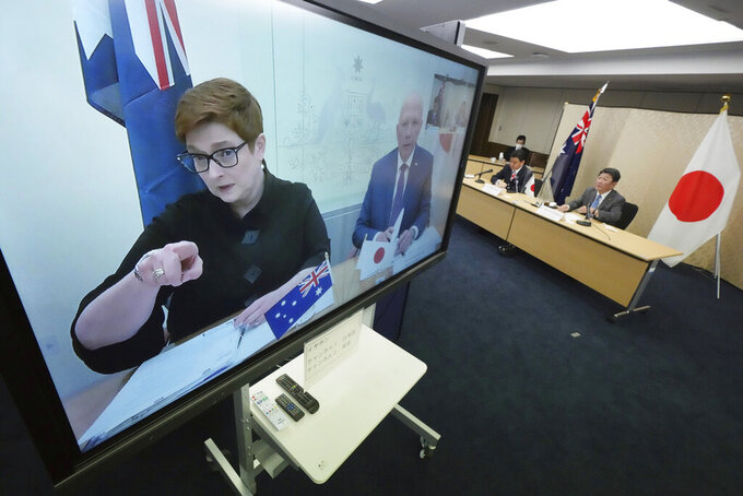 Japanese Foreign Minister Toshimitsu Motegi, right, and Defense Minister Nobuo Kishi, second right, attend a video conference with Australian Foreign Minister Marise Payne, left on screen, and Australian Defense Minister Peter Dutton, right on screen, at Foreign Ministry in Tokyo during their two-plus-two ministerial meeting Wednesday, June 9, 2021, in Tokyo. (AP Photo/Eugene Hoshiko, Pool)