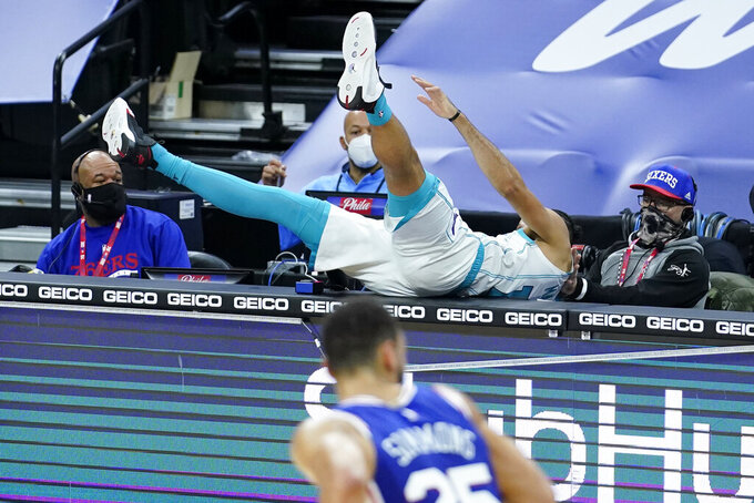 Charlotte Hornets' Caleb Martin, top, flies on top of the scorers table after chasing a loose ball during the first half of an NBA basketball game against the Philadelphia 76ers, Monday, Jan. 4, 2021, in Philadelphia. (AP Photo/Matt Slocum)