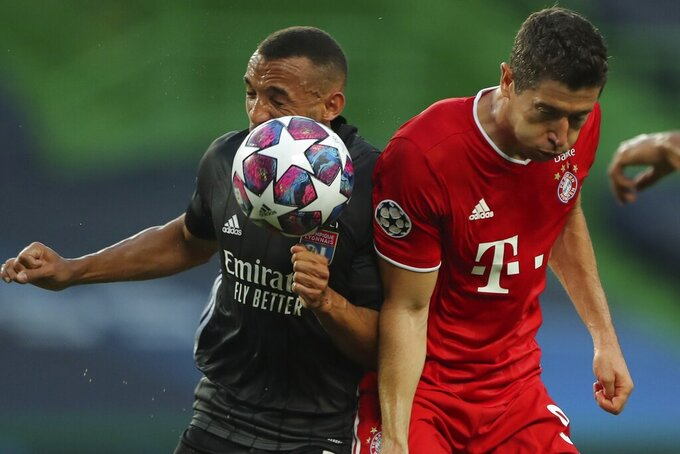 Lyon's Lucas Tousart, left, and Bayern's Robert Lewandowski go for the ball during the Champions League semifinal soccer match between Lyon and Bayern Munich at the Jose Alvalade stadium in Lisbon, Portugal, Wednesday, Aug. 19, 2020. (Miguel A. Lopes/Pool via AP)