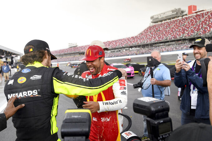 Bubba Wallace, second from left, is congratulated by Ryan Blaney, left, after Wallace was pronounced the winner while on pit row during a rain delay in a NASCAR Cup series auto race Monday, Oct. 4, 2021, in Talladega, Ala. (AP Photo/John Amis)