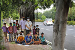 A former diplomat Virendra Gupta and his singer wife Veena Gupta pose for a photograph with underprivileged children whom they teach on a sidewalk in New Delhi, India, on Sept. 3, 2020.  The Indian couple are conducting free classes for underprivileged children on a sidewalk in New Delhi with the goal to keep them learning and not left behind when schools reopen. As most schools in India remain shut since late March when the country imposed a nationwide lockdown to curb the spread of COVID-19, many switched to digital learning and taking classes online. (AP Photo/Manish Swarup)