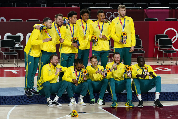 Australia poses for photos on the podium with their bronze medals after beating Slovenia during the men's bronze medal basketball game at the 2020 Summer Olympics, Saturday, Aug. 7, 2021, in Tokyo, Japan. (AP Photo/Charlie Neibergall)
