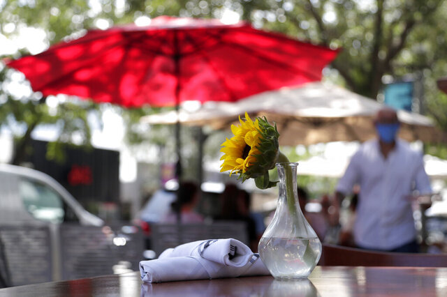 An outdoor table is ready for customers at Loretta and the Butcher restaurant during the coronavirus pandemic, Thursday, Aug. 6, 2020, in the Coconut Grove neighborhood in Miami. Restaurants continue to offer outdoor dining and take-out only, with indoor dining still not permitted in Miami-Dade County. (AP Photo/Lynne Sladky)
