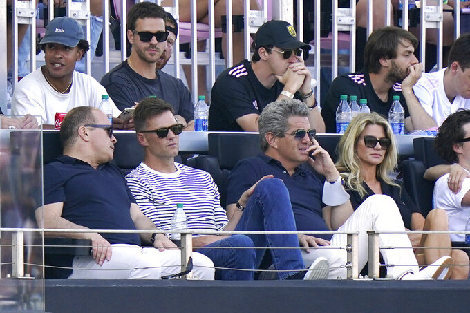 Tampa Bay Buccaneers quarterback Tom Brady, second from front left, watches the second half of an MLS soccer match between Inter Miami and the LA Galaxy, Sunday, April 18, 2021, in Fort Lauderdale, Fla. (AP Photo/Lynne Sladky)