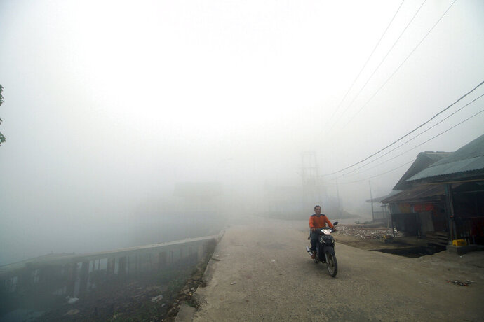 A man rides his motorcycle through the haze from forest fires in Palembang, South Sumatra, Indonesia, Monday, Oct. 14, 2019. Thick, noxious haze from new deliberately set fires blanketed parts of Indonesia's Sumatra island on Monday after days of improving air quality, causing school closings and flight delays. (AP Photo/Iwan Cheristian)