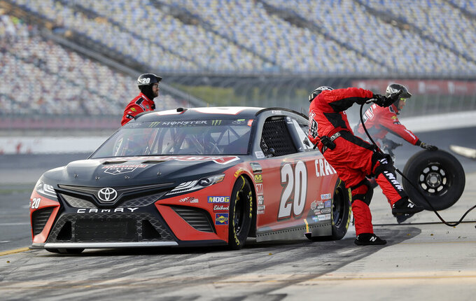A crew member jumps out of the way as Erik Jones leaves following a pit stop during qualifying for Saturday's NASCAR All-Star auto race at Charlotte Motor Speedway in Concord, N.C., Friday, May 17, 2019. (AP Photo/Chuck Burton)