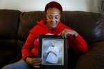In this Oct. 24, 2019, photo, Robbie Brown holds a picture of her deceased son Artaives, who was friends with Myon Burrell when Burrell was arrested and convicted for the 2002 murder of Tyesha Edwards in Minneapolis. Burrell denied being with his friend, and Artaives, questioned separately, also said he was not with Burrell. Robbie Brown, however, said the boys were just protecting one another.