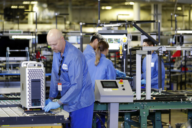 FILE - In this Nov. 20, 2019, file photo, workers are shown at an Apple manufacturing plant in Austin, Texas. American factories slowed for the third consecutive month in May as they continued to sustain economic damage from the coronavirus pandemic. The Institute for Supply Management, an association of purchasing managers, said Monday, June 1, 2020, that its manufacturing index came in at 43.1 last month after registering 41.5 in April. Anything below 50 signals that U.S. manufacturers are in retreat. (AP Photo/ Evan Vucci, File)
