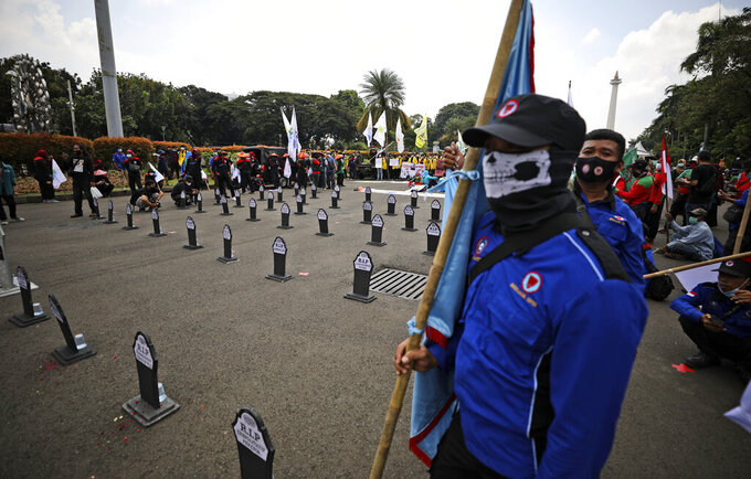 Workers stand near mock graves representing the deaths of labor rights during a May Day rally in Jakarta, Indonesia, Saturday, May 1, 2021. Workers in Indonesia marked international labor day on Saturday curtailed by strict limits on public gatherings to express anger at a new law they say could harm labor rights and welfare. (AP Photo/Dita Alangkara)