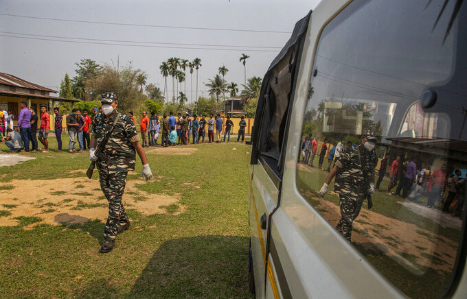 An Indian paramilitary person walks past people standing in queue to cast their votes in a polling station during the third phase of assembly election in Gauhati, India, Tuesday, April 6, 2021. Voters in four Indian states and a union territory are casting their ballots, in elections seen as a test for Prime Minister Narendra Modi's government which is battling the latest surge in coronavirus cases. (AP Photo/Anupam Nath)