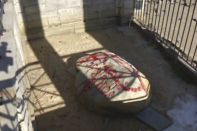 This photo provided by WCVB shows the vandalized Plymouth Rock in Plymouth, Mass., Monday, Feb. 17, 2020. The iconic Plymouth Rock and other sites were covered in red graffiti Monday during a vandalism spree discovered at the site marking the landing of the Pilgrims in Massachusetts 400 years ago. (WCVB via AP)