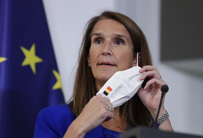 Belgian Prime Minister Sophie Wilmes takes off her protective mask prior to a press conference following the National Security Council meeting on the COVID-19 outbreak, in Brussels, Wednesday, Sept. 23, 2020. Belgium's prime minister announced Wednesday a relaxation of social-distancing rules as part of a less stringent long-term coronavirus strategy, despite the steady rise of COVID-19 cases in a country already hard-hit by the virus. (Olivier Hoslet, Pool via AP)