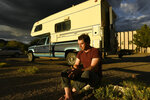 Alex Eherenman, 35, sits outside of camper on June 30, 2021 in Carbondale, Colo.  Eherenman has lived in his truck-bed camper on and off since 2017 trying to make enough at his jobs while trying to save money so he can afford either a security deposit for an apartment or the down payment on an apartment come winter time.  (Helen H. Richardson /The Denver Post via AP)