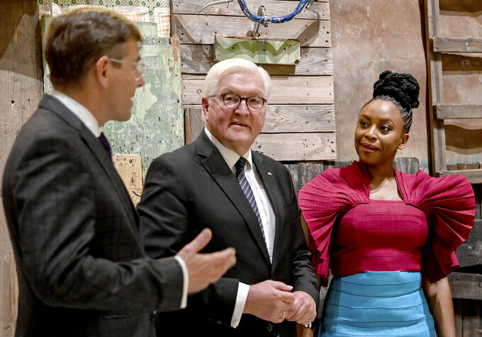 Germany's President Frank-Walter Steinmeier, center, and writer Chimamanda Ngozi Adichie, right, are guided through the exhibition by Hartmut Dorgerloh, General Director and Chairman of the Board of the Humboldt Forum Foundation, left, in the Berlin Palace, Berlin, Germany, Wednesday Sept. 22, 2021, during the ceremony marking the exhibition opening of the Ethnological Museum, the Museum of Asian Art of the National Museums in Berlin/Prussian Cultural Heritage Foundation and the Humboldt Forum Foundation. (Britta Pedersen/Pool via AP)