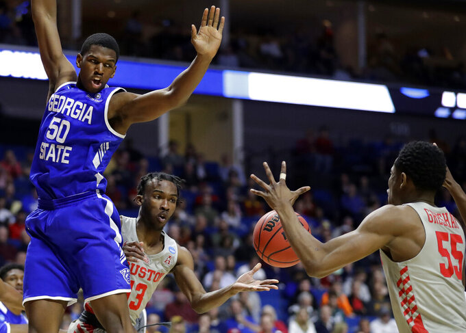 Houston's DeJon Jarreau (13) passes to teammate Brison Gresham (55) as Georgia State's Jordan Tyson (50) watches during the second half of a first round men's college basketball game in the NCAA Tournament Friday, March 22, 2019, in Tulsa, Okla. (AP Photo/Jeff Roberson)