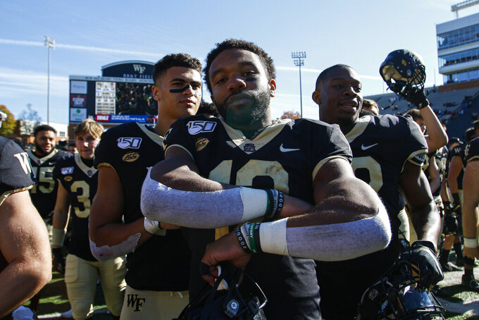 Wake Forest quarterback Jamie Newman, center, stands on the field after leading his team to a 44-10 win over North Carolina State in NCAA college football game in Winston-Salem, N.C., Saturday, Nov. 2, 2019. (AP Photo/Nell Redmond)