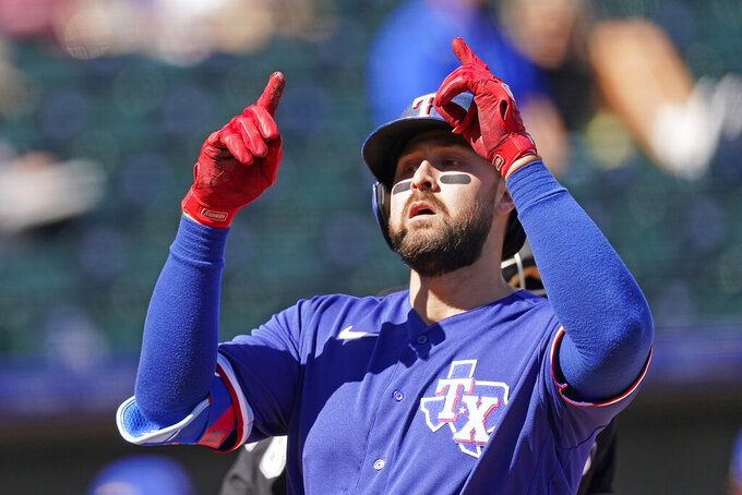 FILE - Texas Rangers' Joey Gallo celebrates as he crosses the plate after hitting a two-run home run during the first inning of a spring training baseball game against the Kansas City Royals, in Surprise, Ariz., in this Sunday, Feb. 28, 2021, file photo. Gallo went into spring training trying to lower his launch angle, straighten up his posture and hit more line drives. The Texas Rangers slugger wasn't worried about trying to hit home runs. (AP Photo/Charlie Riedel, File)