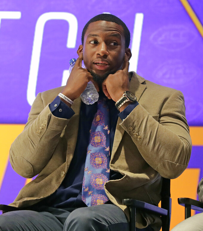 FILE - In this July 19, 2018, file photo, Clemson's Clelin Ferrell covers his ears as a teammate speaks during a news conference at the NCAA Atlantic Coast Conference college football media day in Charlotte, N.C. The talented defensive end is near the top of most mock NFL drafts and was a first-round candidate this time a year ago when he announced he would return to school for a shot at another crown. The second-ranked Tigers take on No. 1 Alabama for the national title on Monday night, Jan. 7, 2019. (AP Photo/Chuck Burton, File)