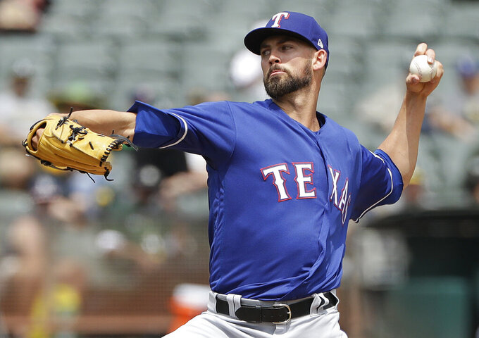 FILE - In this Aug. 22, 2018, file photo, Texas Rangers pitcher Mike Minor throws against the Oakland Athletics during the first inning of a baseball game, in Oakland, Calif. The Rangers have a completely revamped starting rotation with lone returner Mike Minor and four pitchers who have had Tommy John surgery.  (AP Photo/Jeff Chiu, File)