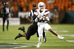 Hawaii defensive back Rojesterman Farris II (4) tries to pull down Arizona wide receiver Stanley Berryhill III (86) in the second half of an NCAA college football game, Saturday, Aug. 24, 2019, in Honolulu. (AP Photo/Marco Garcia)