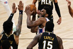 Philadelphia 76ers center Joel Embiid (21) is defended by Atlanta Hawks' John Collins (20) and Clint Capela (15) as he looks for an opening during the first half of Game 6 of an NBA basketball Eastern Conference semifinal series Friday, June 18, 2021, in Atlanta. (AP Photo/John Bazemore)
