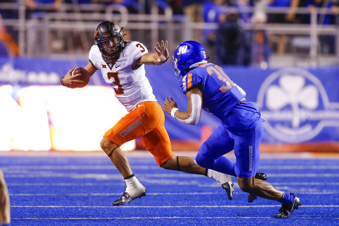 Oklahoma State quarterback Spencer Sanders (3) looks to fend off Boise State defensive end Isaiah Bagnah (30) during the second half of an NCAA college football game Saturday, Sept. 18, 2021, in Boise, Idaho. (AP Photo/Steve Conner)