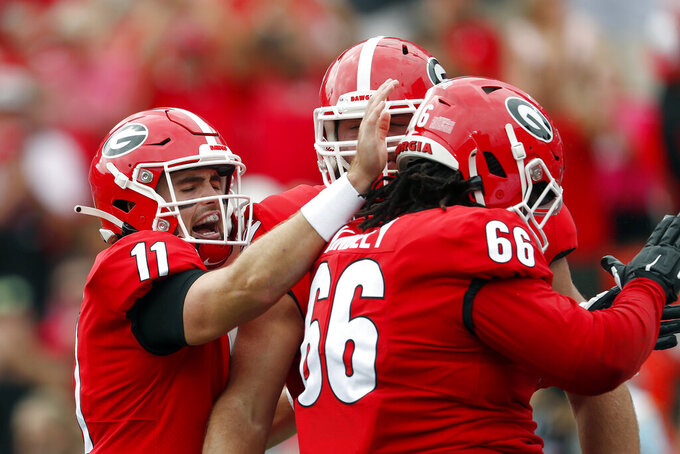 Georgia quarterback Jake Fromm (11) celebrates with offensive lineman Solomon Kindley (66) after throwing a touchdown pass in the first half of an NCAA college football game against Arkansas State Saturday, Sept. 14, 2019, in Athens, Ga. (AP Photo/John Bazemore)