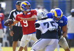 Los Angeles Rams quarterback Matthew Stafford looks for a receiver while Dallas Cowboys defensive tackle Osa Odighizuwa rushes during NFL football practice Saturday, Aug 7, 2021, in Oxnard, Calif. (AP Photo/John McCoy)