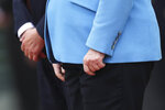 The hands of German Chancellor Angela Merkel, right, and Finland's Antti Rinne as they listen to the national anthems at the chancellery in Berlin, Wednesday, July 10, 2019. Merkel's body shook visibly as she stood alongside the Finnish prime minister and listen to the national anthems during the welcoming ceremony at the chancellery. (AP Photo/Markus Schreiber)