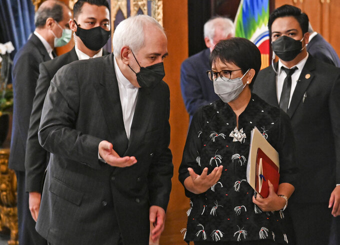 In this photo released by Indonesian Ministry of Foreign Affairs, Indonesian Foreign Minister Retno Marsudi, right, talks with her Iranian counterpart Mohammad Javad Zarif during their meeting in Jakarta, Indonesia, Monday, April 19, 2021. (Indonesian Ministry of Foreign Affairs via AP)
