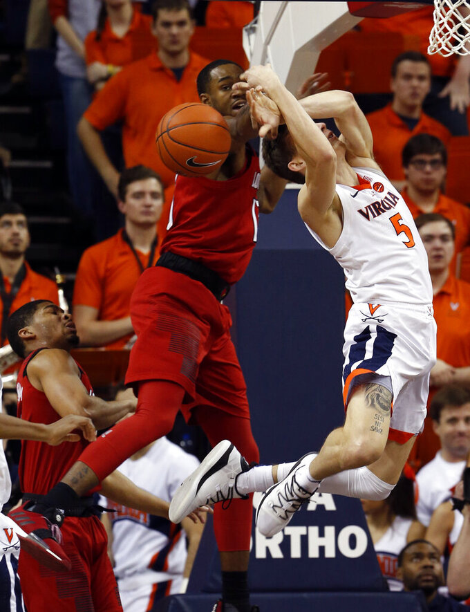 Louisville guard Christen Cunningham (1) strips the ball from Virginia guard Kyle Guy (5) during the first half of an NCAA college basketball game in Charlottesville, Va., Saturday, March 9, 2019. (AP Photo/Steve Helber)