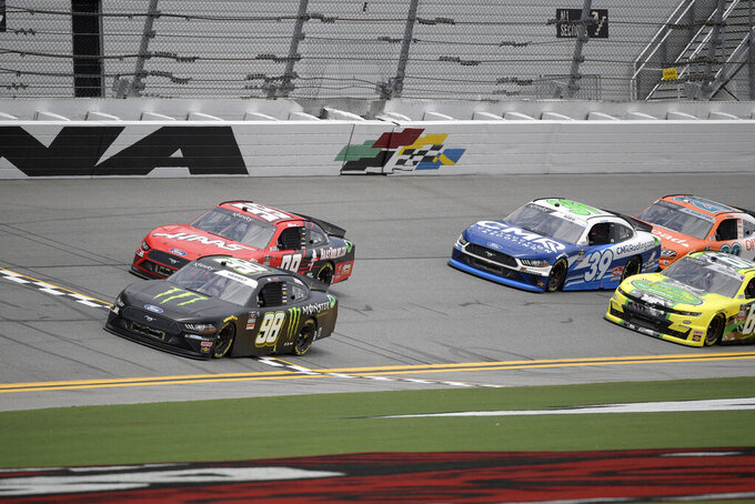 Riley Herbst (98) leads a group of drivers along the front stretch during a NASCAR Xfinity Series auto race at Daytona International Speedway, Saturday, Aug. 28, 2021, in Daytona Beach, Fla. (AP Photo/Phelan M. Ebenhack)