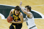 Iowa guard Austin Ash (13) drives on Michigan State guard Jack Hoiberg (10) in the second half of an NCAA college basketball game in East Lansing, Mich., Saturday, Feb. 13, 2021. (AP Photo/Paul Sancya)