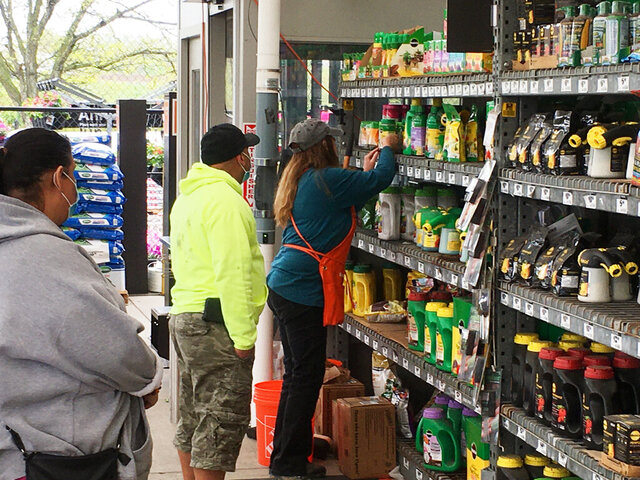 A clerk assists customers at the garden center at a Home Depot store in Harrisburg, Pa., on Wednesday, May 6, 2020. As swaths of Pennsylvania prepare for a limited reopening Friday, some fed-up business owners are jumping the gun and have resumed serving customers in defiance of Gov. Tom Wolf's shutdown order. Home Depot said Wednesday that
