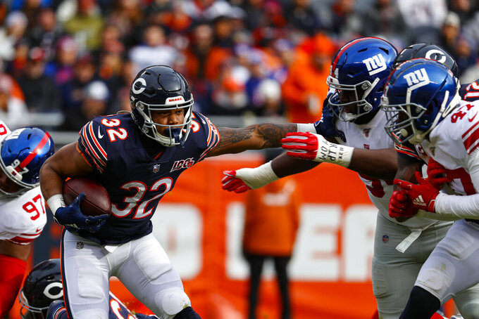 Chicago Bears running back David Montgomery (32) pushed off New York Giants defensive end Dalvin Tomlinson (94) and outside linebacker Alec Ogletree (47) during the first half of an NFL football game in Chicago, Sunday, Nov. 24, 2019. (AP Photo/Paul Sancya)