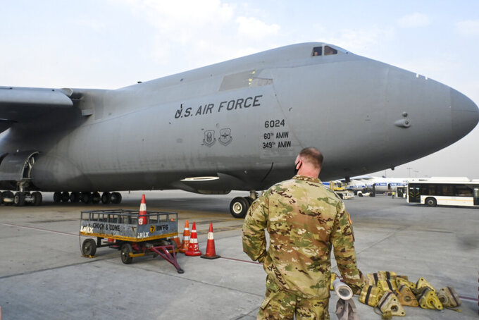 A U.S. Air Force aircraft carrying relief supplies from the United States in the wake of India's COVID-19 situation arrives at the Indira Gandhi International Airport cargo terminal in New Delhi, India, Friday, April 30, 2021. (Prakash Singh/Pool via AP)