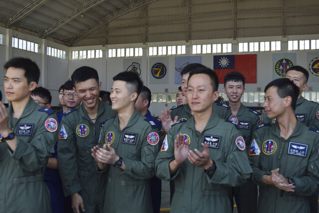 Taiwanese airmen applaud as they listen to Taiwan President Tsai Ing-wen speak during her visit to the Penghu Magong military air base in outlying Penghu Island, Taiwan Tuesday, Sept. 22, 2020. Tsai visited the military base on one of Taiwan's outlying islands Tuesday in a display of resolve following a recent show of force by rival China. (AP Photo/Wu Huizhong)