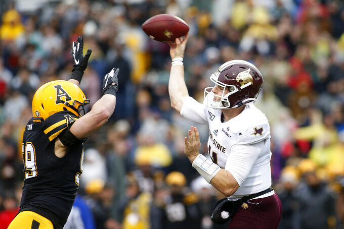 Texas State quarterback Tyler Vitt (11) throws to an open receiver while getting pressure from Appalachian State linebacker Jordan Fehr (59) during the first half of an NCAA college football game Saturday, Nov. 23, 2019, in Boone, N.C. (AP Photo/Brian Blanco)